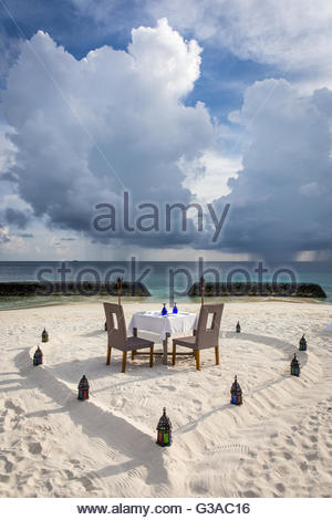 Maldives, Ari Atoll, Moofushi Resort, Table for a romantic dinner on the beach - Stock Photo