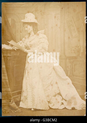 An elegant Victorian woman in an elaborate white dress:  Mrs Sassoon, possibly an  actress.      Date: late 19th - Stock Photo