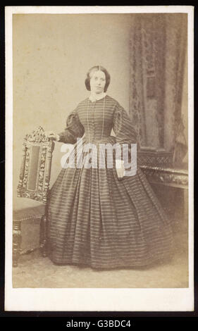 A dress in a horizontally  striped fabric with front  buttoning bodice, gigot  sleeves, white cuffs & collar, - Stock Photo