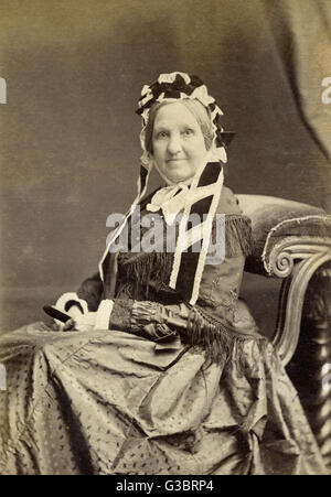 Middle-aged Victorian woman in a studio portrait, smiling at the camera.      Date: circa 1860s - Stock Photo