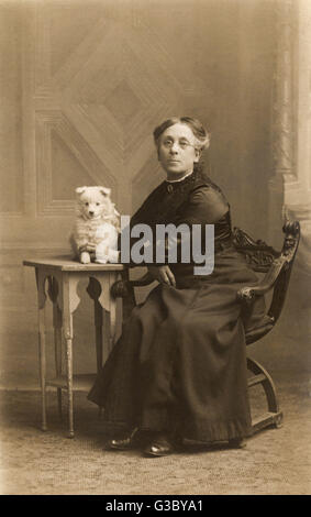 A middle aged woman with a small white dog in a studio photo.      Date: circa 1900 - Stock Photo