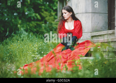 Woman in red Victorian dress sitting on stairs - Stock Photo