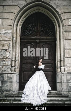 Mysterious woman in Victorian dress with old doors - Stock Photo
