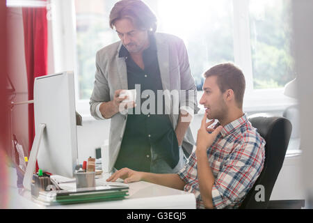 Businessmen drinking coffee and working at computer in office - Stock Photo