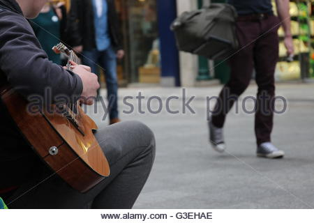 'Busk', A busker musician playing guitar  on a street in Ireland- Color - Stock Photo