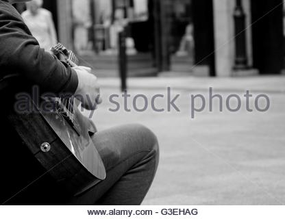 'Busk', A busker musician playing guitar  on a street in Ireland- Monochrome - Stock Photo