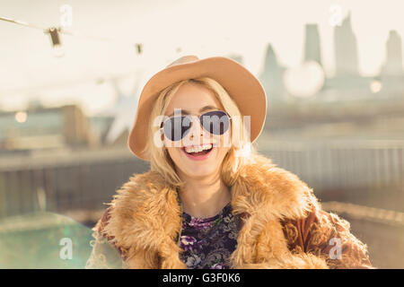 Portrait enthusiastic young woman wearing hat and sunglasses on sunny rooftop - Stock Photo