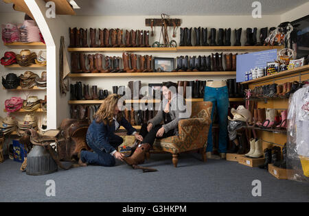 Shop assistant helping customer with boots - Stock Photo