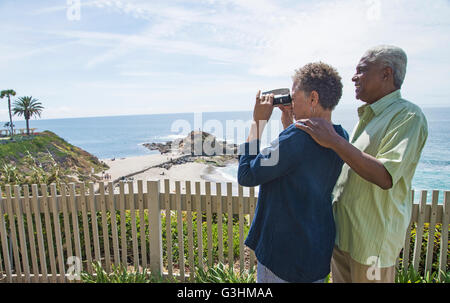 Senior couple outdoors, woman looking through binoculars, looking at view - Stock Photo