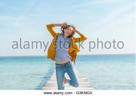 Mid adult woman dancing on pier, wearing headphones - Stock Photo