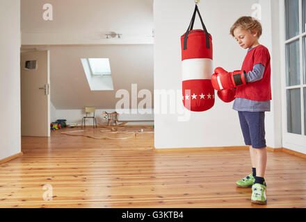 Boy with punch bag putting on boxing gloves - Stock Photo
