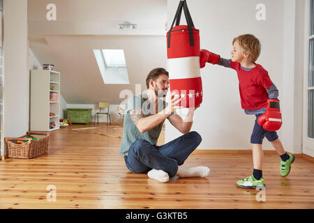 Father holding punchbag for son - Stock Photo