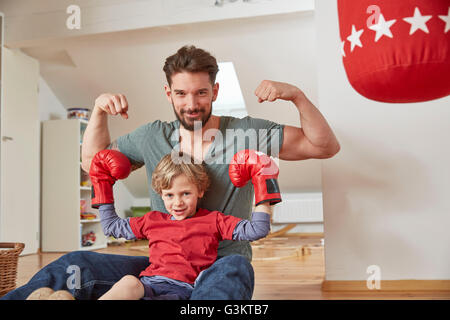 Boy wearing boxing with father, flexing muscles looking at camera - Stock Photo