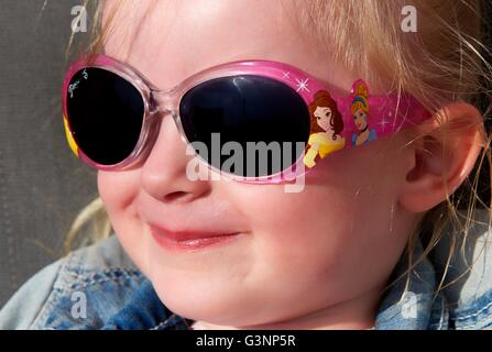 A three year old toddler girl laughing wearing sunglasses - Stockfoto