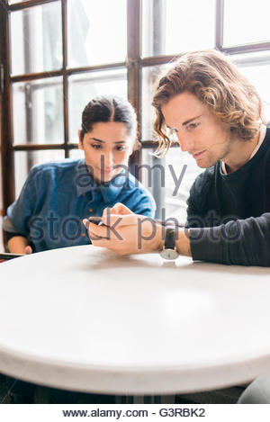 Sweden, Young people looking at mobile phone in cafe - Stock Photo