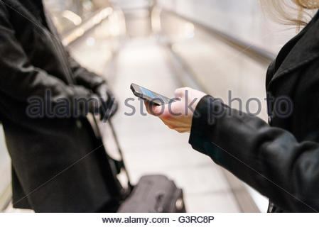 Sweden, Skane, Malmo, Mid section of woman texting on escalator - Stock Photo