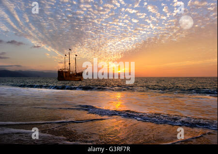 Pirate ship fantasy is an old wooden pirate ship with full flags as the sun sets on the ocean and the moon rises - Stock Photo