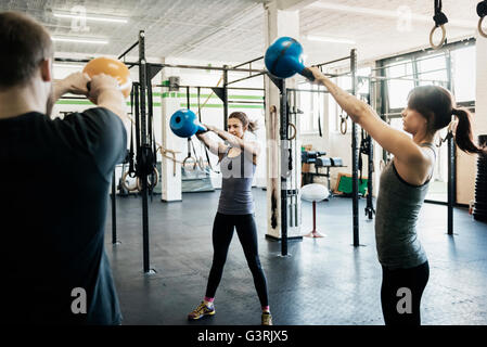Germany, Young women and man swinging kettlebells in gym - Stock Photo