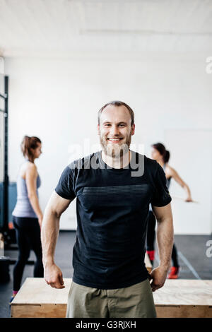 Germany, Young man and women standing in gym - Stock Photo