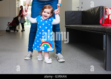 Toddler (girl) learning to walk - Stock Photo