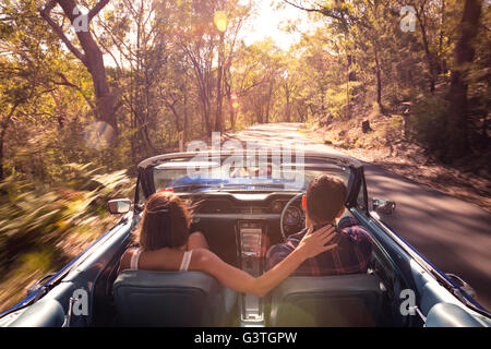 Australia, New South Wales, Sydney, Lane Cove, Couple driving car through forest - Stock Photo
