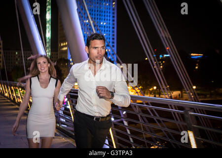 A smartly dressed couple run across the Millennium Bridge in London at night. - Stock Photo