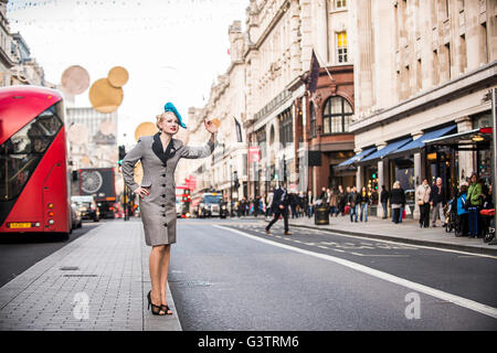 A stylish young woman dressed in 1930s style clothing hailing a taxi on Regent Street in London. - Stock Photo