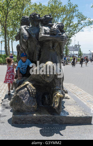 Two children enjoying climbing on The Immigrants sculpture in Battery Park, New York, on a sunny day - Stock Photo