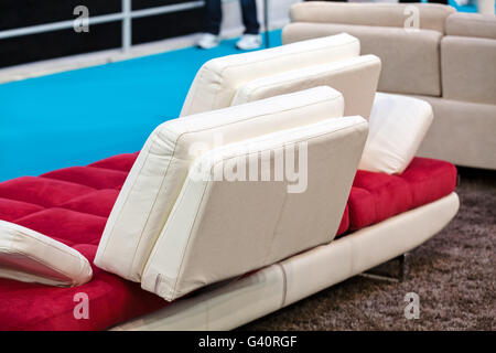 red couch with four wight rectangle pillows; note shallow depth of field - Stock Photo