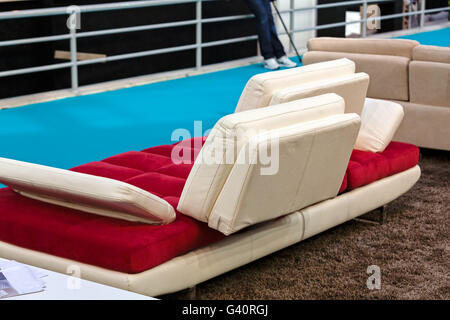 red couch with four wight rectangle pillows - Stock Photo