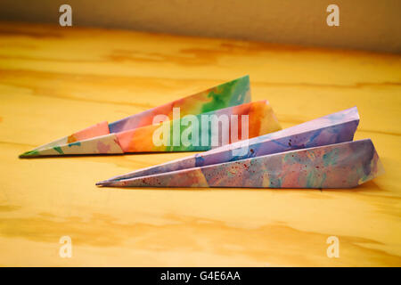 Photograph of some paper colorful planes on a wood table - Stock Photo