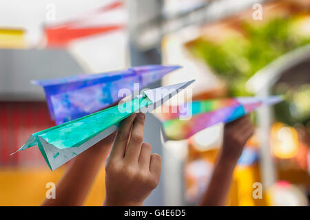 Photograph of some paper colorful planes on ready to fly on children hands - Stock Photo