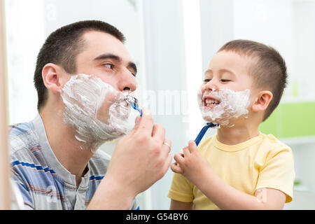 happy child have fun with dad shaving in the bathroom - Stock Photo
