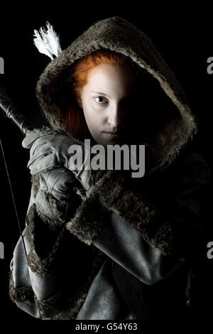 girl archer in a costume with bow isolated in a dark background - Stockfoto