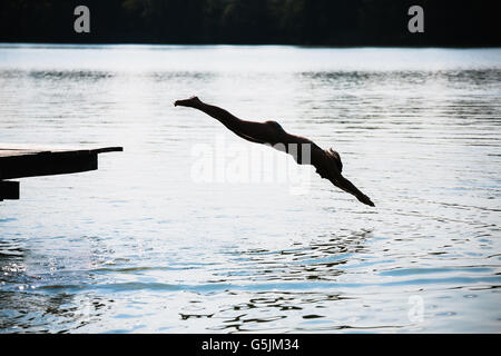 woman jumping into the lake - Stockfoto