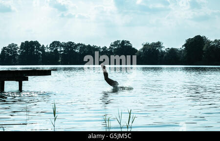 woman jumping into the lake - Stockfoto