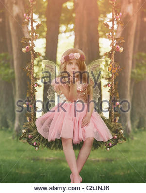 A little girl is in the woods on a swing with sparkle fairy wings blowing magical dust for an imagination or fairy - Stock Photo
