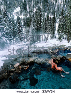 Forest in winter, man sitting in a hot spring. - Stock Photo