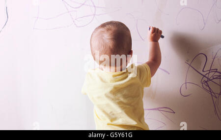 Baby boy drawing with wax crayon on plasterboard wall. He is with his back towards - Stockfoto