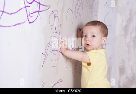 Baby boy drawing with wax crayon on plasterboard wall. He is looking to the camera - Stockfoto