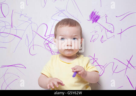 Baby boy with wax crayon on plasterboard wall. He is looking to the camera - Stockfoto