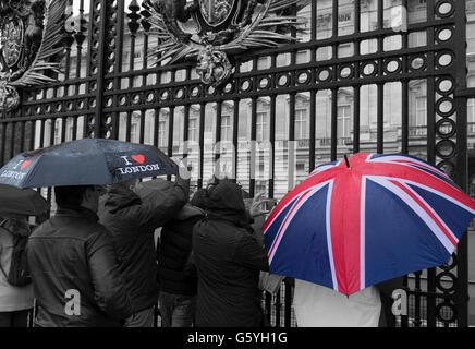 LONDON, ENGLAND - OCTOBER 21, 2015: Tourists looking through a gate of Buckingham palace on a rainy day. Buckingham - Stock Photo