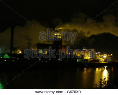 Dramatic night view of an industrial building illuminated against a smoky sky - Stock Photo