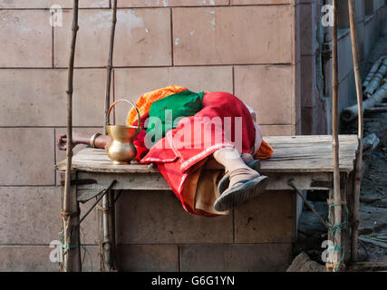 Indian woman sleeping on wooden table in the street. The major tradition followed in the area - Stock Photo