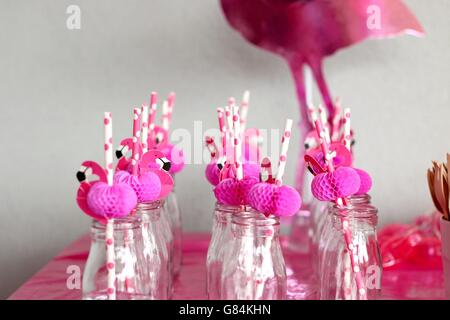 Pink flamingo straws in glass bottles in a row - Stockfoto