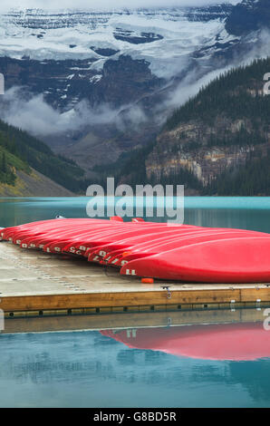 Red canoes on dock, Lake Louise, Banff National Park - Stock Photo