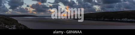 A panorama or panoramic image of the sunset on Crantock Beach, near Newquay in Cornwall, UK. - Stock Photo