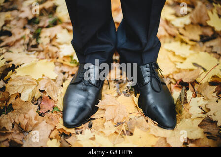 Closeup groom's wedding shoes on the ground with golden leafs in autumn - Stockfoto