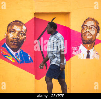 Las Palmas, Gran Canaria, Canary Islands, Spain, 30th June 2016. A man walks past a wall painted with images of - Stock Photo