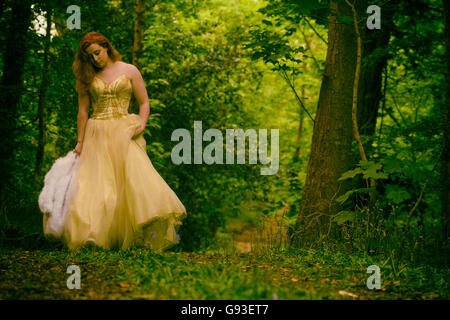 Fantasy makeover / fashion / portrait photography - a woman wearing a large billowing ball gown walking alone along - Stockfoto